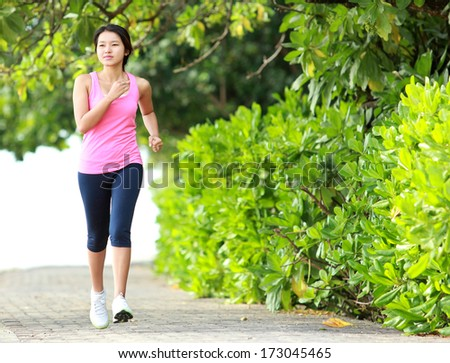 Beautiful fitness model in pink running on the beach - stock photo