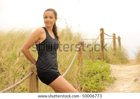 Beautiful fitness model relaxing at post on beach dunes trail.