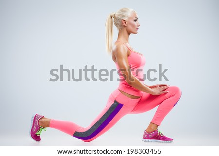 Beautiful fitness model stretches the muscles on a gray background - stock photo