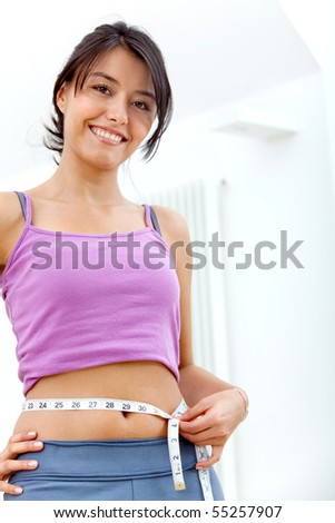 Beautiful fitness woman in sportswear measuring her waist indoors - stock photo