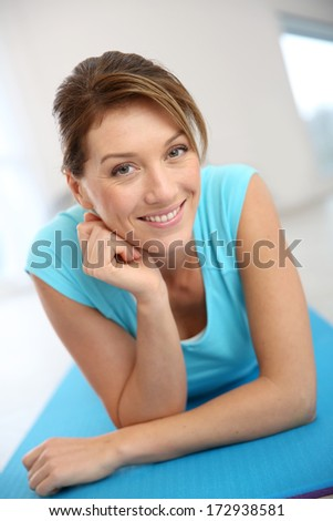Beautiful fitness woman laying in gym floor - stock photo