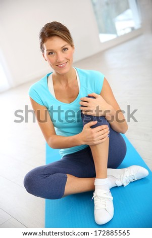 Beautiful fitness woman sitting in gym - stock photo