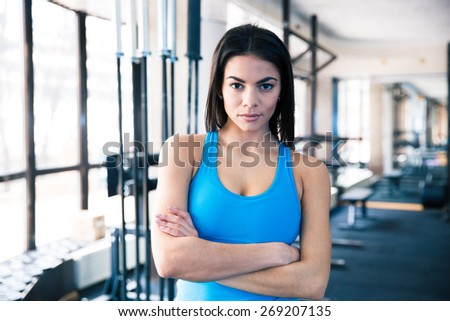 Beautiful fitness woman with arms folded standing in fitness gym - stock photo