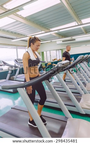 Beautiful fitness woman with towel over her neck training on a treadmill in fitness center - stock photo