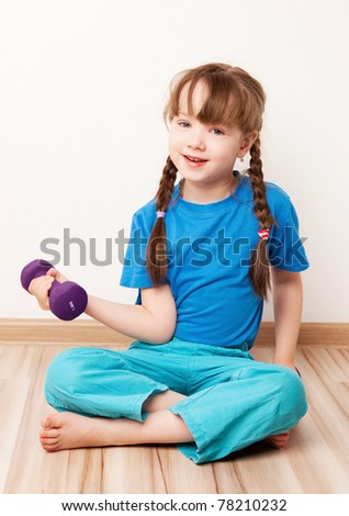 beautiful five year old girl working out with  dumbbells at home