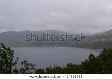 beautiful fjord landscape in summer with heavy rainfall and mountain backdrop