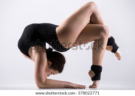 Beautiful flexible young athlete woman in black leotard working out, doing art gymnastics backbend pose, acrobatic exercise, full length, studio, white background, isolated - stock photo