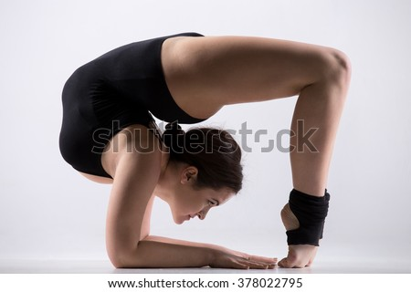 Beautiful flexible young athlete woman in black leotard working out, doing variation of bridge pose, acrobatic exercise, full length, studio, white background, isolated - stock photo