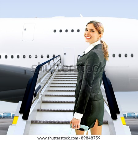 beautiful flight attendant near moving ramp in airport - stock photo