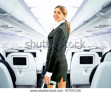 beautiful flight attendant on board of big plane - stock photo