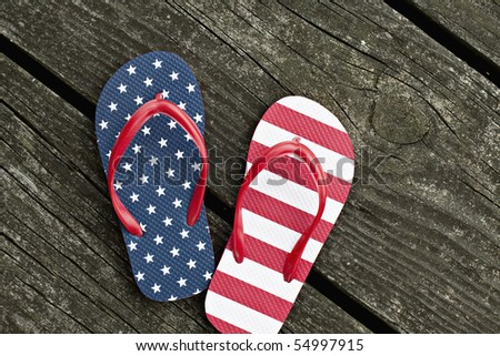 Beautiful flip flops, one with stars and the other with stripes, sitting outdoors on old weathered wooden pier that has moss and lichens on it. - stock photo
