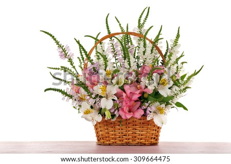 Beautiful floral arrangement in basket isolated on white - stock photo