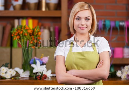 Beautiful florist at working place. Beautiful young female florist keeping arms crossed and looking at camera while standing near her working place  - stock photo