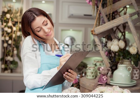 Beautiful florist is standing in her flower shop and talking on the phone with her client. She is listening to her customer attentively and smiling. The woman is writing down the main ideas - stock photo