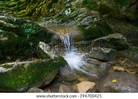 Beautiful flow of water flowing between the stones - stock photo