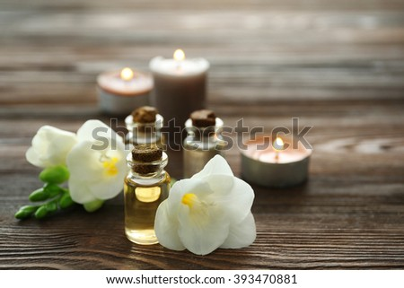 Beautiful flower, aroma oil and candles on wooden background