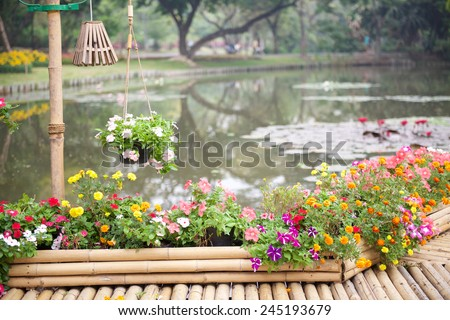 Beautiful flower garden with bamboo path over lotus pond - stock photo