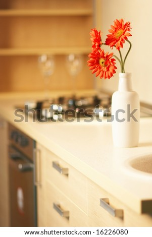 Beautiful flower on table in modern white kitchen - stock photo