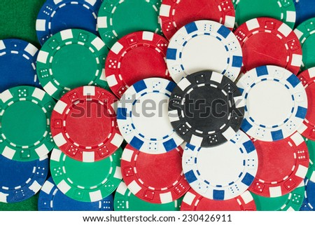Beautiful flower tower made of Black, White, Green, Blue and Red Playing Poker Chips in a green background