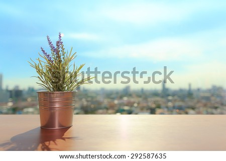 Beautiful flower vase near a window and have a cityscape on a background. - stock photo