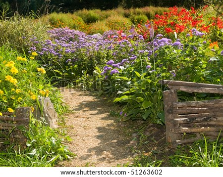 Beautiful flowerbed behind rural retro fences - stock photo