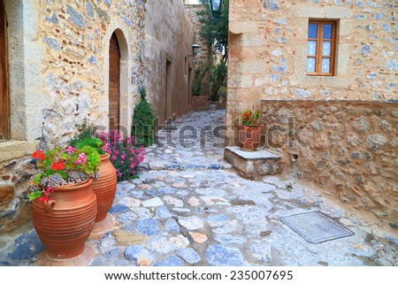 Beautiful flowers decorate narrow streets inside the Byzantine town of Monemvasia, Greece - stock photo