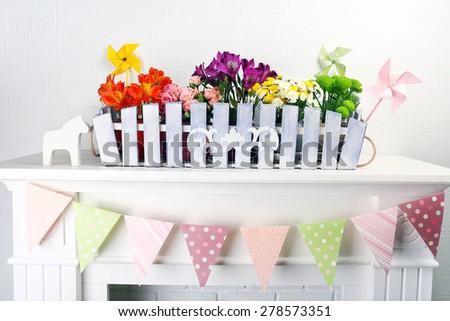 Beautiful flowers in ornamental flowerpot on mantelpiece - stock photo