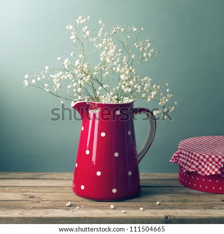 Beautiful flowers in red jug on wooden table - stock photo