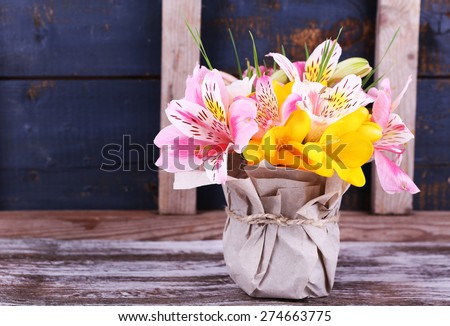Beautiful flowers in vase on wooden background - stock photo