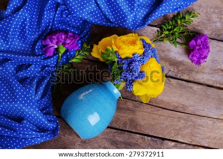 Beautiful flowers in vase on wooden background top view - stock photo