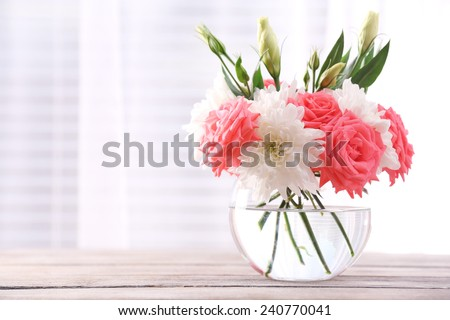 Beautiful flowers in vase with light from window - stock photo