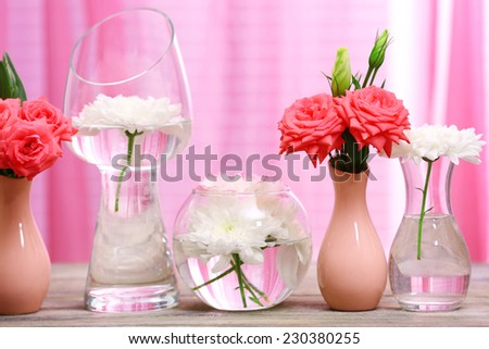 Beautiful flowers in vases on table on curtains background