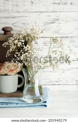 Beautiful flowers in vases on wooden background - stock photo