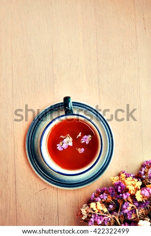 Beautiful flowers of the field on a wooden table with a cup of black tea. Background. top view