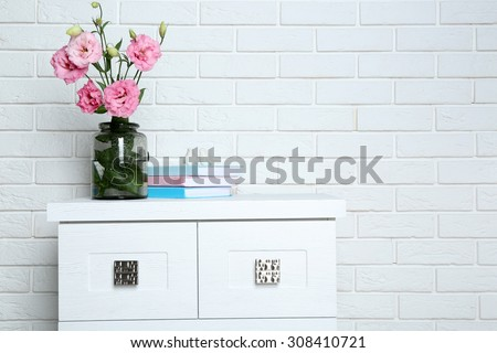 Beautiful flowers with books on brick wall background - stock photo