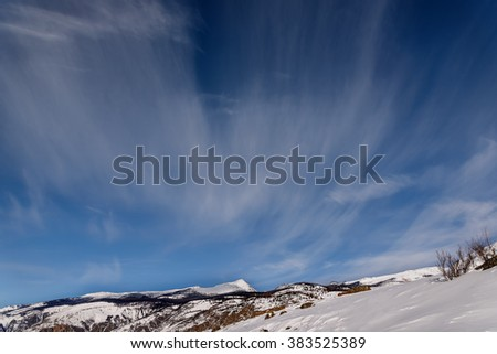 Beautiful fluffy clouds on a blue sky on a background of mountains covered with snow and vegetation winter - stock photo