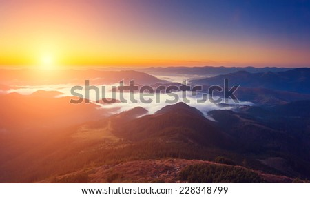 Beautiful foggy hills glowing by sunlight at twilight. Dramatic scene. Colorful sky. Carpathian, Ukraine, Europe. Beauty world.