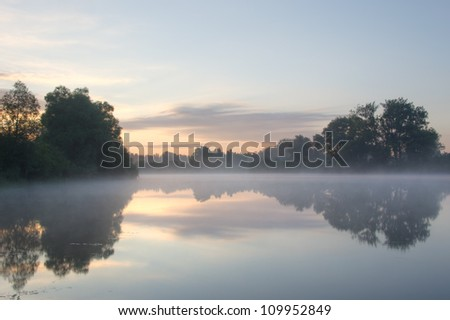 Beautiful foggy sunrise on a lake in the Netherlands.