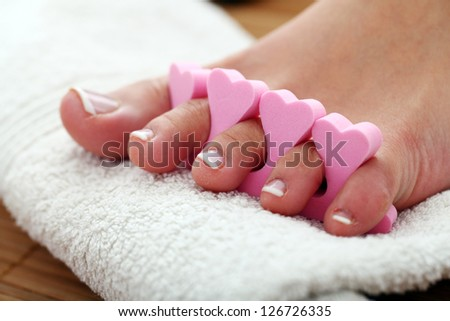Beautiful foot with french pedicure on white towel - stock photo
