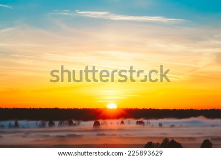 Beautiful Forest On Sunrise. Dramatic Sky With Sunrise Sun Over Morning Fog On Meadow - stock photo