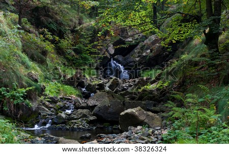 Beautiful forest waterfall with stream. - stock photo