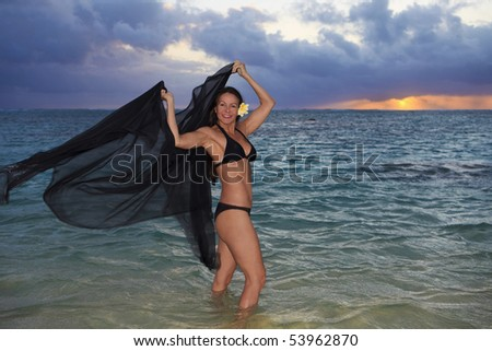 beautiful forty year old woman in the ocean at sunrise in hawaii - stock photo