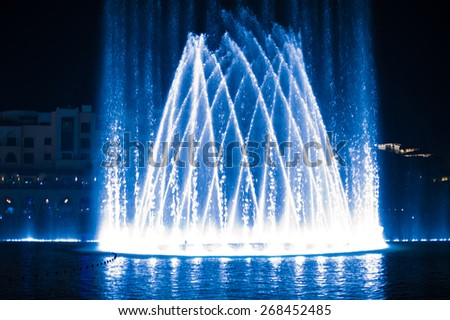Beautiful fountain at night illuminated with blue light. - stock photo