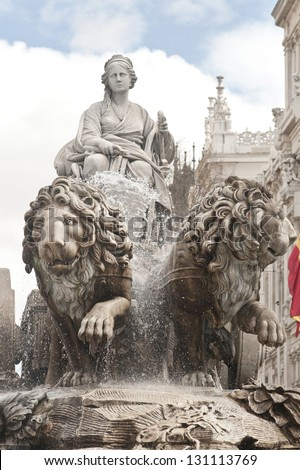 Beautiful fountain of the Roman mother goddess Cibeles in a chariot pulled by two dramatic lions. In central Madrid.  The old Post Office, Correos, now the Town Hall is in the background with flags. - stock photo