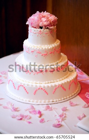 Beautiful Four Tiered Wedding Cake With Pink Icing and Pink Flowers. - stock photo