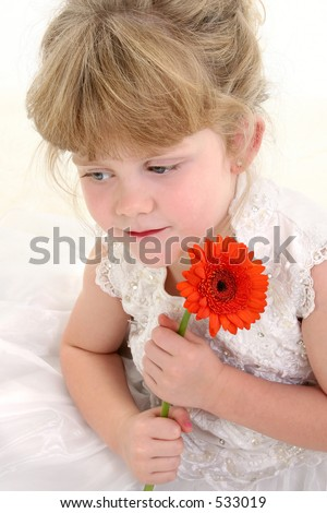 Beautiful four year old girl holding flower. Shot in studio over white Wearing white pageant dress and hair up. - stock photo