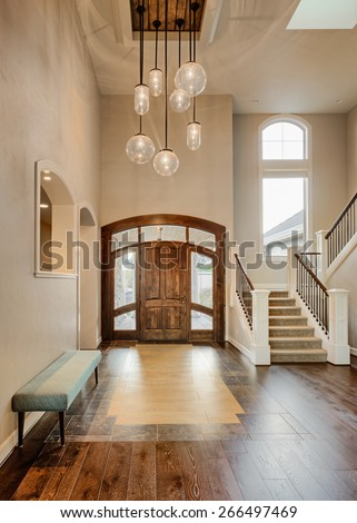 Beautiful Foyer in Home; Entryway with Stairs, Pendant Lights, Hardwood Floor, Tile, Bench, and Vaulted Ceilings in New Luxury House - stock photo