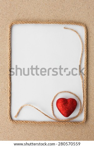 Beautiful frame of rope and red heart with a white background on the sand, with place for your image, text - stock photo