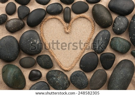 Beautiful frame of rope in the form of heart with black stones, on the sand - stock photo
