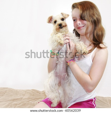 Beautiful freckled brunette female child holds cute white lap dog